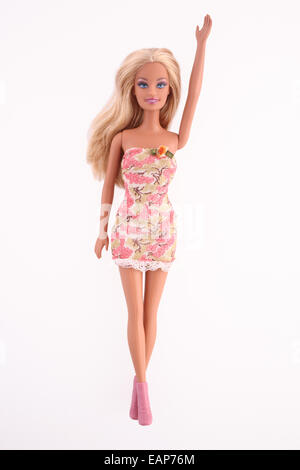 Barbie doll wearing a pink dress, one arm raised, isolated on white background. - Stock Image