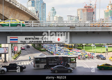Thai-Japan Friendship Bridge with city skyline in the background and heavy traffic in the foreground in Bangkok, Thailand. - Stock Image