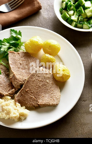 Boiled beef with potatoes and horseradish (tafelspitz) on brown background. - Stock Image