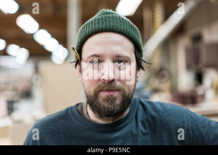 A portrait of a Caucasian carpenter working in a large woodworking shop. - Stock Image