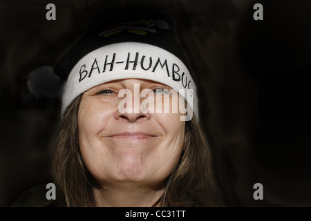 middle-aged woman wearing bah humbug hat - Stock Image