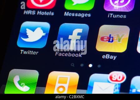 Detail macro image of the iphone touch screen. Display shows apps from facebook, twitter, ebay, itunes and messages - Stock Image