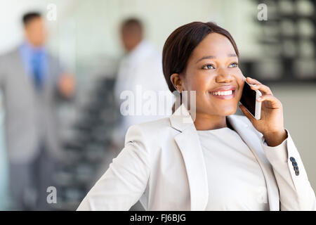 happy young businesswoman talking on cell phone in modern office - Stock Image