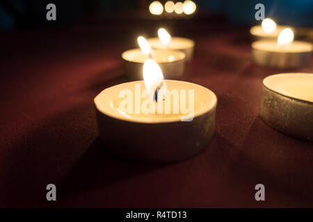 Tealight candles burning the flames dimly illuminating the area. - Stock Image