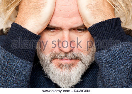 Concerned man rests head on his hands - Stock Image
