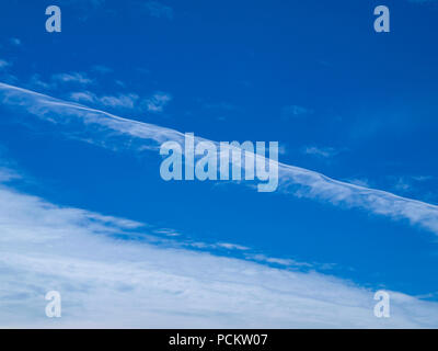 A brightly coloured Contrail and Cirrus sky cloudscape featuring a vapor trail cloud formation in a mid blue sky. New South Wales, Australia. - Stock Image