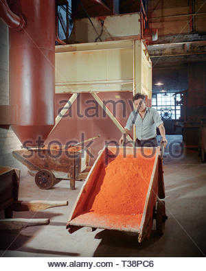 Wheeling a wooden wheel barrow load of raw materials from the mixing facility to the glass furnaces at Whitefriars Glass, London,England, UK – 1970s (1970) - Stock Image