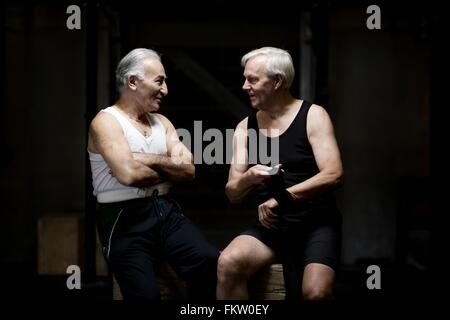 Two senior men chatting and preparing in dark gym - Stock Image