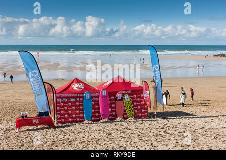 Colourful tents and banners for a surfing competition on Fistral Beach in Newquay in Cornwall. - Stock Image