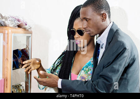 Happy couple pointing fingers at items in a shop window. - Stock Image