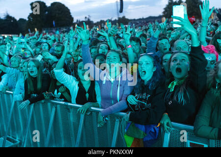 Young music fans at an outdoor music festival in the United Kingdom. Teenagers at a music festival, music festival crowd, teenage girls cheering, starstruck music fans. The festival pictured is Latitude Festival. - Stock Image