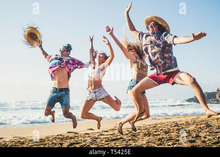 Happiness and youthful generation people have fun together in friendship at the ebach for summer holiday vacation jumping like crazy and laughing a lo - Stock Image