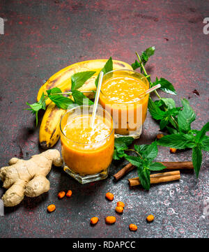 Sea-buckthorn smoothie with banana and mint. On rustic background. - Stock Image