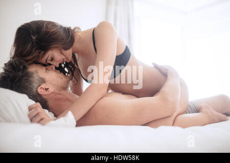 Erotic woman on top of man lying on bed. Sensual young couple making love in bedroom. - Stock Image