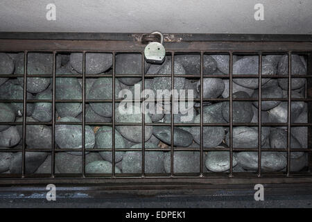 large rocks under locked grate - Stock Image