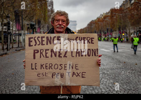 Paris, France. 1st December, 2018.  Man holding a sign reading 'fuel too expensive, take the plane' during the Yellow Vests protest against Macron politic. Credit: Guillaume Louyot/Alamy Live News - Stock Image