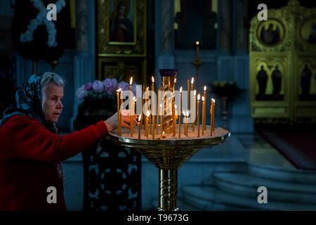 Elderly woman lighting a candle near the iconostasis in the Central Saint Vladimir's Cathedral (burial vault of admirals) in Sevastopol, Crimea - Stock Image