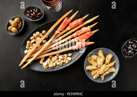 Italian antipasti. Prosciutto-wrapped Italian grissini with olives, artichokes, and wine, shot from the top on a black background - Stock Image