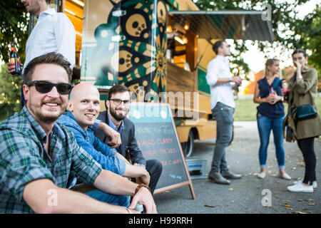Group of customers relaxing next to food truck - Stock Image