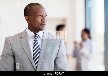 thoughtful afro American business man looking outside the window - Stock Image
