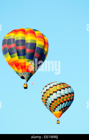 A pair of colourful hot air balloon in flight with blue sky behind during the Bristol Balloon fiesta held annually - Stock Image