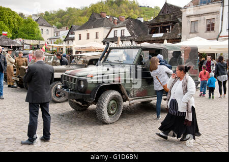 Gypsy woman and Rally VI military vehicles from World War II in Kazimierz Dolny, antique army Willys cars event - Stock Image