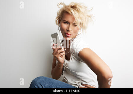 Stylish Female Making Selfie Smartphone While Standing Against White Background Listening Music Earphones.Copy Space - Stock Image