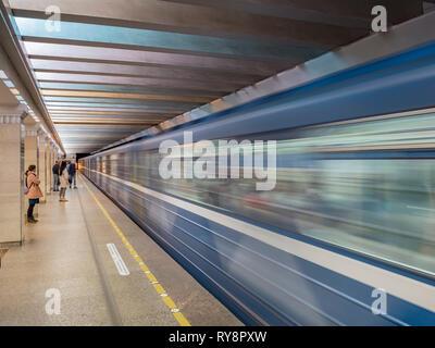 18 September 2018: St Petersburg, Russia - Train entering Sportivnaya station on the St Petersburg Metro as passengers wait on the platform. - Stock Image