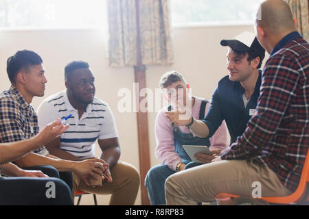 Men talking n group therapy circle - Stock Image