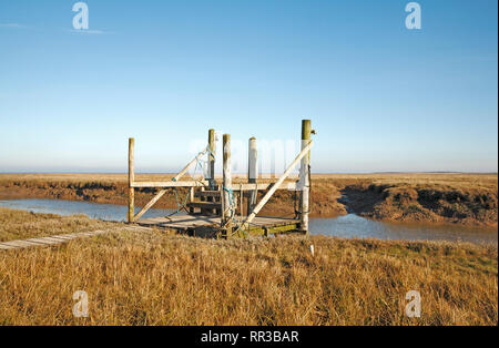A boat landing stage and mooring point on the quayside at the North Norfolk harbour at Thornham, Norfolk, England, United Kingdom, Europe. - Stock Image