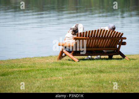 A man and woman sitting on a park bench at Osborne Point on Lake Pleasant in Speculator, NY USA reading the newspaper. - Stock Image