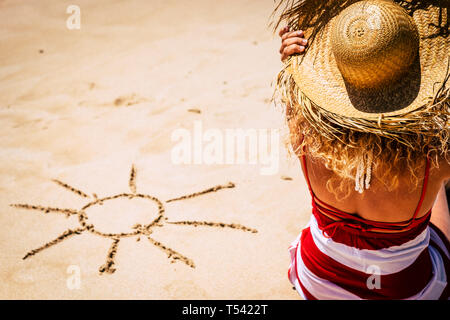 Summer holiday vacation concept with girl sitting on the beach and sun deisgned on the sand - above view of tourist people enjoying the sunbath - cauc - Stock Image