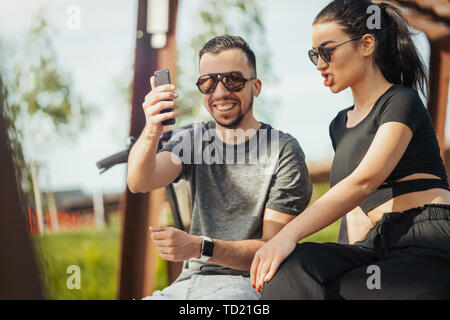 Couple of young man and woman sitting in park and making selfie. - Stock Image