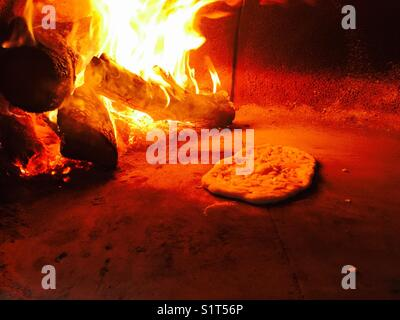 Wood fire oven pizza cooking - Stock Image