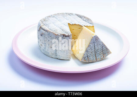 Round mature French Tomme cheese with one cutted piece on white board isolated close up - Stock Image