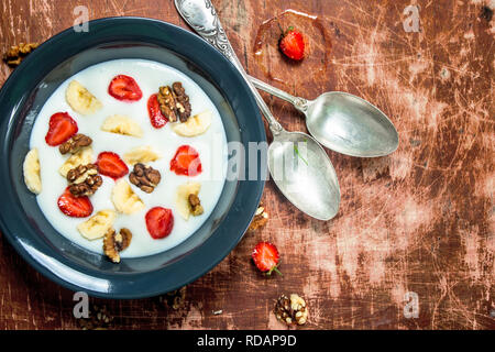 Semolina porridge with strawberries and nuts. On rustic background. - Stock Image