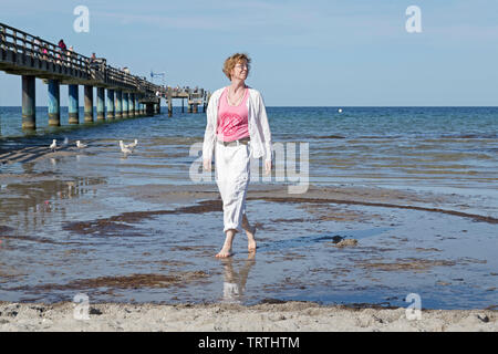 woman wading through the water, beach, Boltenhagen, Mecklenburg-West Pomerania, Germany - Stock Image