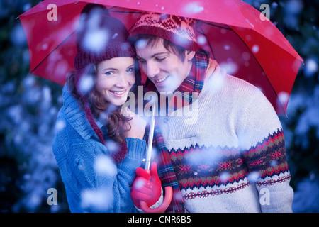 Smiling couple under umbrella in snow - Stock Image