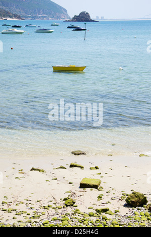 A yellow boat on a beach. - Stock Image