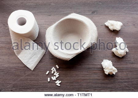 Feeling unwell concept with sick bowl, toilet roll and tablets - Stock Image