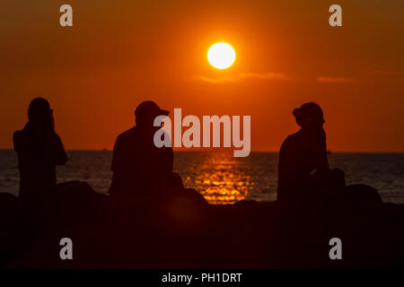 People sit on the jetty and watch the sunset over the Vineyard Sound at Menemsha Beach in Chilmark, Massachusetts on Martha's Vineyard. - Stock Image
