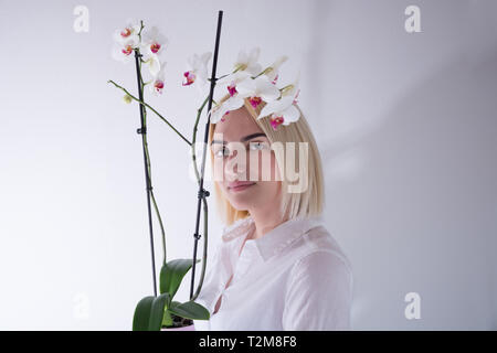 Young woman holding an orchid flower in a pot isolated on white background in studio. Girl looking at camera. Close up, selective focus - Stock Image