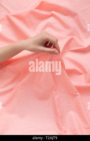 Hand of woman holding pink fabric - Stock Image