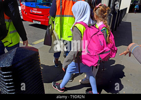 London, England, UK. Group of schoolchildren waiting to get on a bus - one Muslim girl with a headscarf - Stock Image