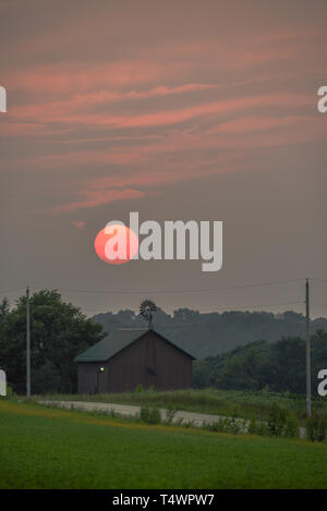 Sultry sunset over rural barn and windmill along countryside road in summer, Monroe, Wisconsin, USA - Stock Image