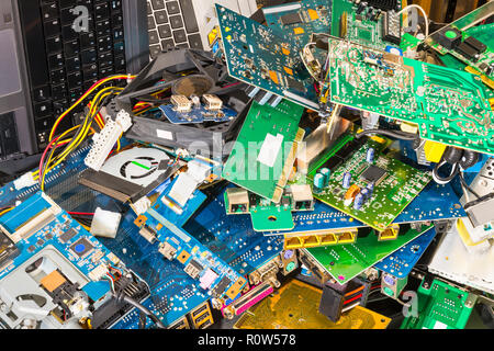 E-waste pile from discarded laptop parts. Connectors, PCB, notebook keyboards. Colorful background from PC components. Recycling of electronic waste. - Stock Image