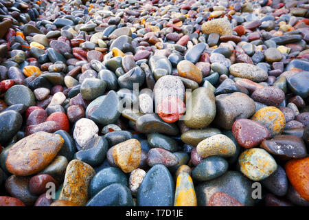 Close up view of beautiful pastel colored wet pebbles at the seashore - Stock Image