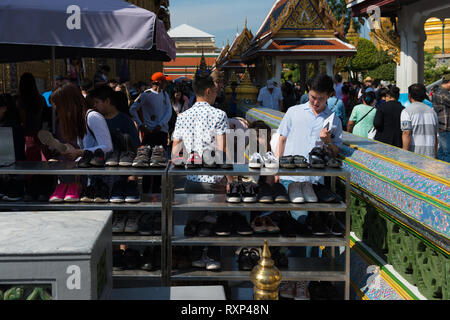 Stand with shoes for tourists near the Temple of Emerald Buddha, Bangkok, Thailand - Stock Image