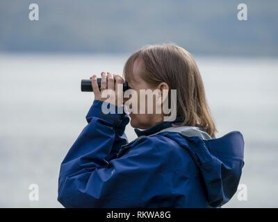 Woman using binoculars to spot marine wildlife in sea Loch Slapin, Isle of Skye, Scotland, UK - Stock Image