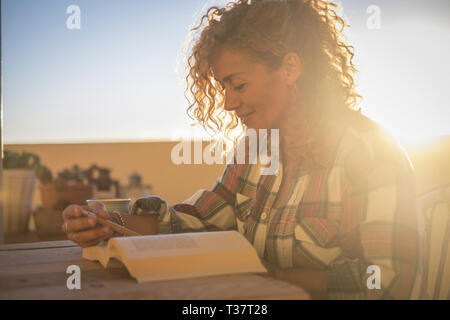 Beautiful happy smiling relaxing caucasian curly blonde woman reading a book dunring the sunlight sunset on the terrace outdoor at home - hipster fema - Stock Image